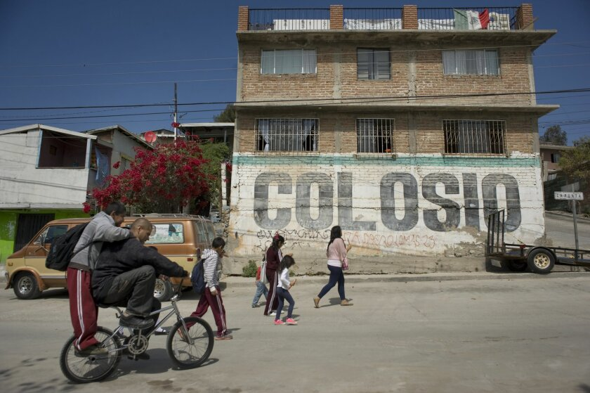 People walk past a wall with an old campaign sign for Luis Donaldo Colosio on Friday in Tijuana's Lomas Taurinas neighborhood, near the spot where presidential candidate was slain on March 23, 1994. ,