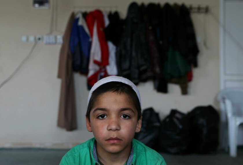 """In this April 19, 2015 picture, Syrian boy Ahmad, 7, whose parents went missing in Syria, attends a class of religious lessons at an Islamic teaching center designed to counter Islamic State group indoctrination, near the Turkish-Syrian border city of Sanliurfa, southern Turkey. """"They are planting"""