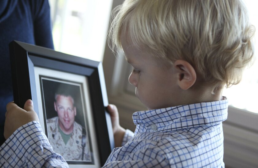 Nathan Murzyn, 2, looks at a picture of his father Marine veteran Russell Murzyn, who died by suicide.