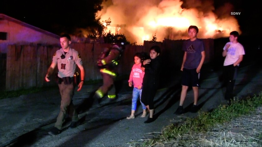 A sheriff's deputy leads children to safety after a Lemon Grove home caught fire.