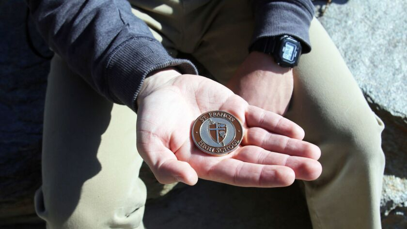 Danny Bozanic, 17, a junior at St. Francis High School holds the very first SFHS President's Coin he