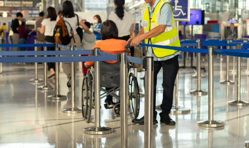 Caretaker with senior woman in a wheelchair at the airport.