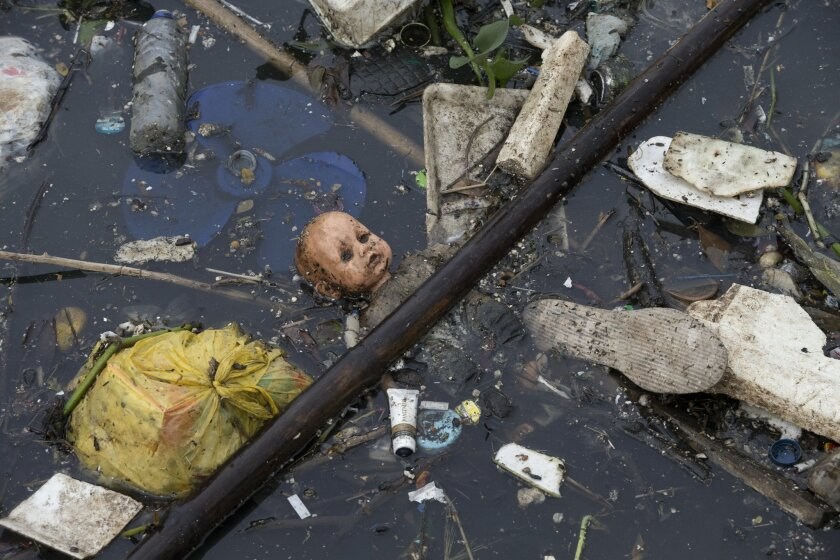 FILE - In this Nov. 5, 2015, file photo, trash floats in the Meriti River, which flows into Guanabara Bay in Rio de Janeiro, Brazil. A major Brazilian daily said Tuesday, Feb. 9, 2016, that the Rio de Janeiro state governor wants to use money earmarked for an environmental fund to cover shortfalls