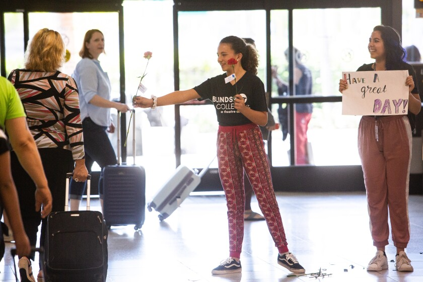"""Olivia Mitchell (center) and Sofia Zaragoza take part in the Blindspot Collective residency project """"Connecting Flights"""" at the San Diego International Airport."""