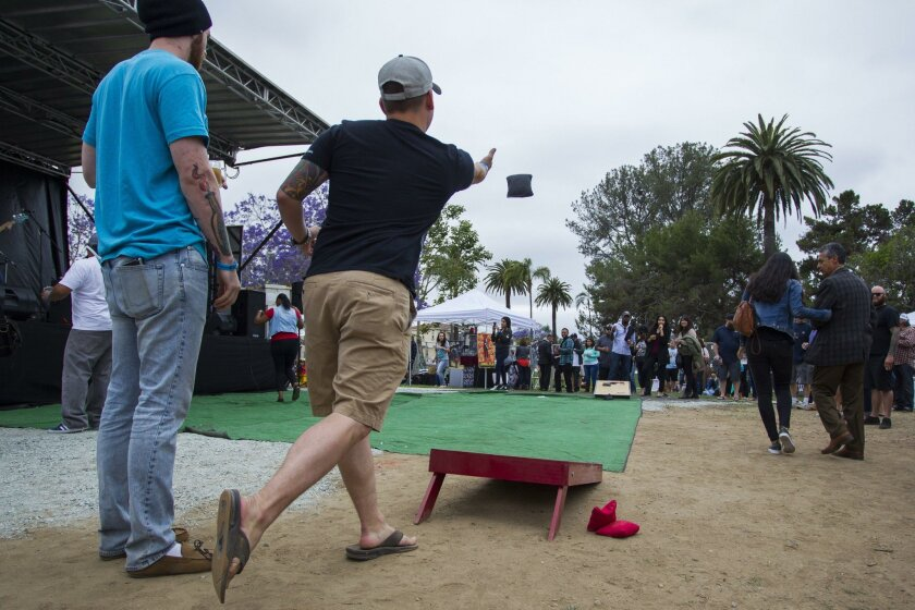 Caleb Guest throws a beanbag during a game of corn hole with friends as the music blasts from the stage.