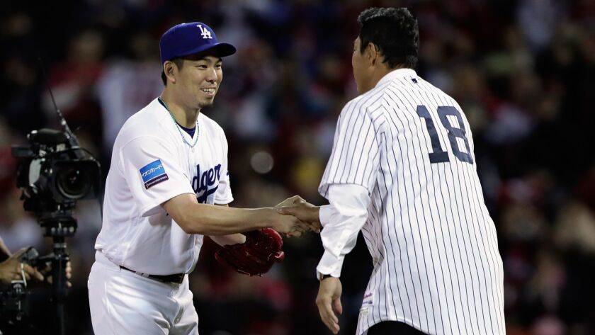 Former pitcher Hiroki Kuroda shakes hands with Pitcher Kenta Maeda of the Dodgers after throwing a ceremonial first pitch prior to the Game 4 between Japan and MLB All Stars.