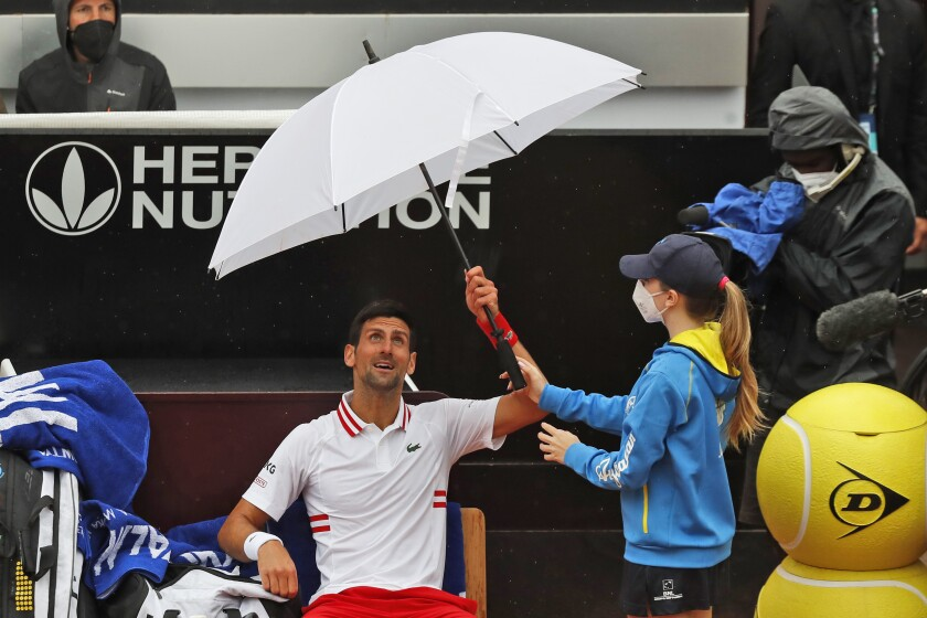 Novak Djokovic of Serbia holds an umbrella during a pause of his match against Taylor Fritz of the United States at the Italian Open tennis tournament, in Rome, Tuesday, May 11, 2021. (AP Photo/Alessandra Tarantino)