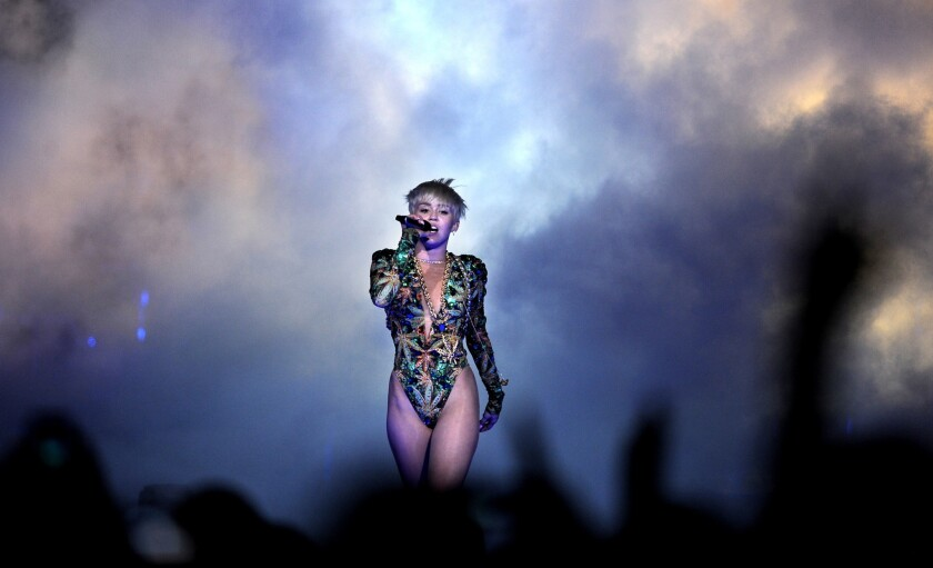 Miley Cyrus emerges from a cloud of smoke wearing a shiny green one-piece reminiscent of the 1990s.