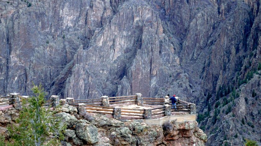 At Gunnison Point, not far from the South Rim Visitor Center, people stare at Black Canyon and the G