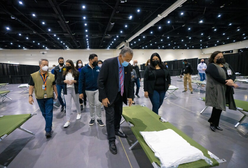 At San Diego Convention Center on Saturday, Congressman Juan Vargas takes a close look at one of the sleeping cots