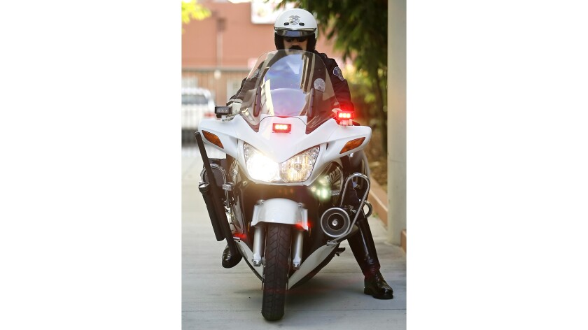A motor officer with flashing lights.