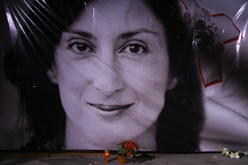 FILE - In this Tuesday, Oct. 16, 2018 file photo, flowers and a candle lie in front of a portrait of slain investigative journalist Daphne Caruana Galizia during a vigil outside the law courts in Valletta, Malta. After a long process of compiling evidence and witness testimony, indictment on charges of complicity in the murder and for criminal conspiracy was filed against Yorgen Fenech, a hotelier whom investigators believe masterminded the killing. (AP Photo/Jonathan Borg, File)