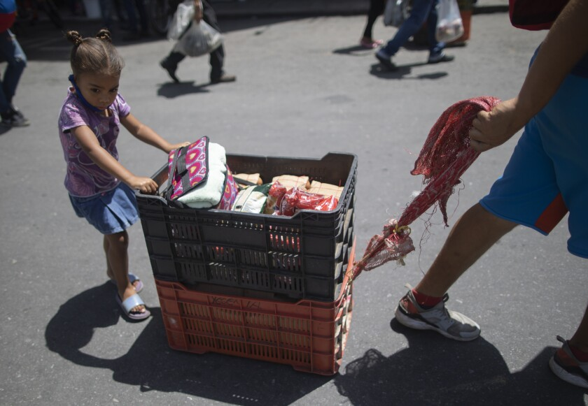 A girl helps to push baskets with products that her family has for sale at a street market during a government-ordered lockdown to curb the spread of COVID-19 in Caracas, Venezuela, Wednesday, July 8, 2020. (AP Photo/Ariana Cubillos)