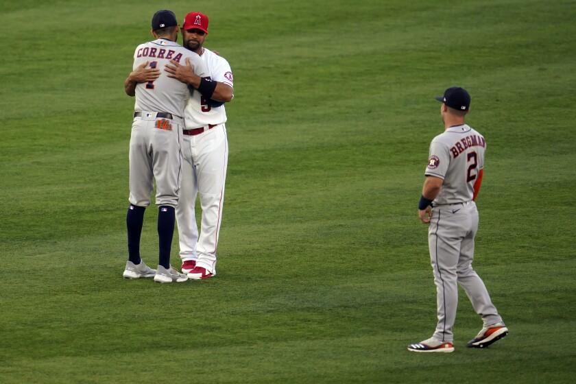 Albert Pujols hugs Carlos Correa with Alex Bregman nearby.