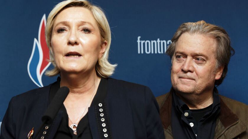 National Front leader Marine Le Pen speaks at the party's annual congress in Lille, France, as former Trump advisor Stephen K. Bannon stands behind her.