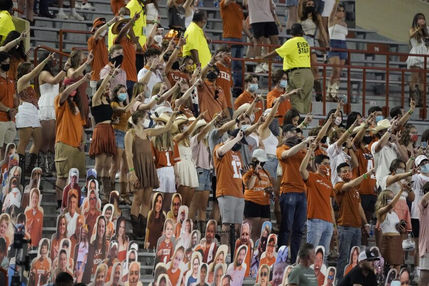 """FILE - In this Saturday, Sept. 12, 2020, file photo, fans join in singing """"The Eyes of Texas"""" after Texas defeated UTEP 59-3 in an NCAA college football game in Austin, Texas. Texas athletic director Chris Del Conte said Wednesday, Oct. 14, 2020, he expects players to """"stand together as a unified group"""" to show appreciation for the school and fans during the playing of the school song """"The Eyes of Texas"""" after games, but didn't say what will happen if they refuse. The song has exploded into a thorny controversy after several football players and other athletes said over the summer they no longer wanted to sing it because of its uncomfortable connections to racist elements of the school's past. (AP Photo/Chuck Burton, File)"""