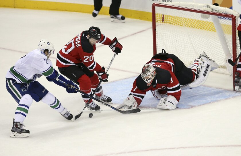 Vancouver Canucks defenseman Ben Hutton (27) tries to score a goal as New Jersy Devils right wing Lee Stempniak (20) helps out goalie Keith Kinkaid (1) with the stop during the second period of an NHL hockey game, Sunday, Nov. 8, 2015, Newark, N.J. (AP Photo/Mel Evans)