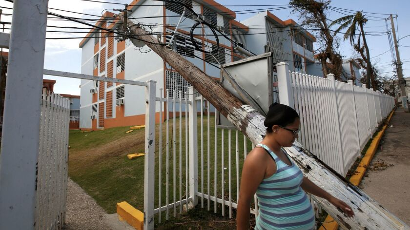 In downtown San Juan, electric lines lie in the road and poles block apartment complexes, like the R