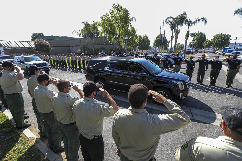 SAN BERNARDINO, CA - SEPTEMBER 22: A hearse carrying casket of fallen Big Bear Interagency Hotshot Charles Morton leaves in a procession from San Bernardino County Coroner's Division main office on Tuesday, Sept. 22, 2020 in San Bernardino, CA. (Irfan Khan / Los Angeles Times)