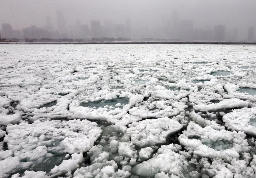 The Chicago skyline and a freezing Lake Michigan are seen from the Museum Campus in Chicago on Sunday, Jan. 5, 2014. Sunday night temperatures will drastically drop to about minus 20 degrees. (AP Photo/Nam Y. Huh)