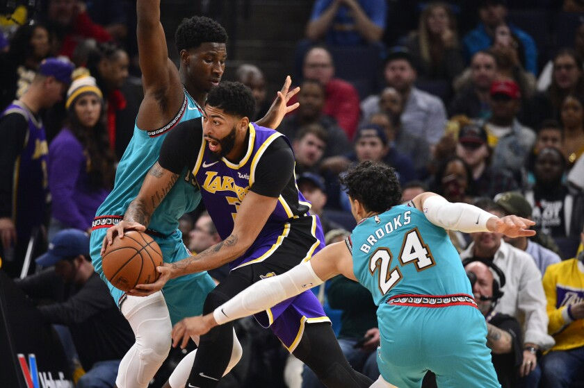 The Lakers' Anthony Davis tries to split the double-team defense of the Grizzlies' Jaren Jackson Jr. and Dillon Brooks.