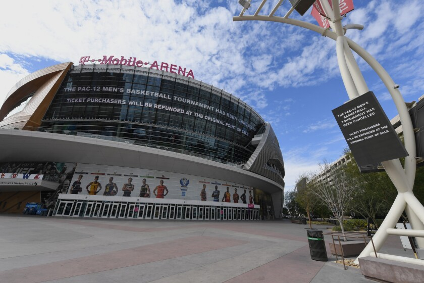 Messages on an LED video wall and a digital sign inform fans of the cancellation of the Pac-12 men's basketball tournament at T-Mobile Arena.
