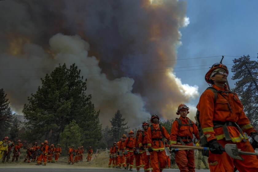 Hand crews march to fight the Cranston fire raging along Highway 74 in Mountain Center.