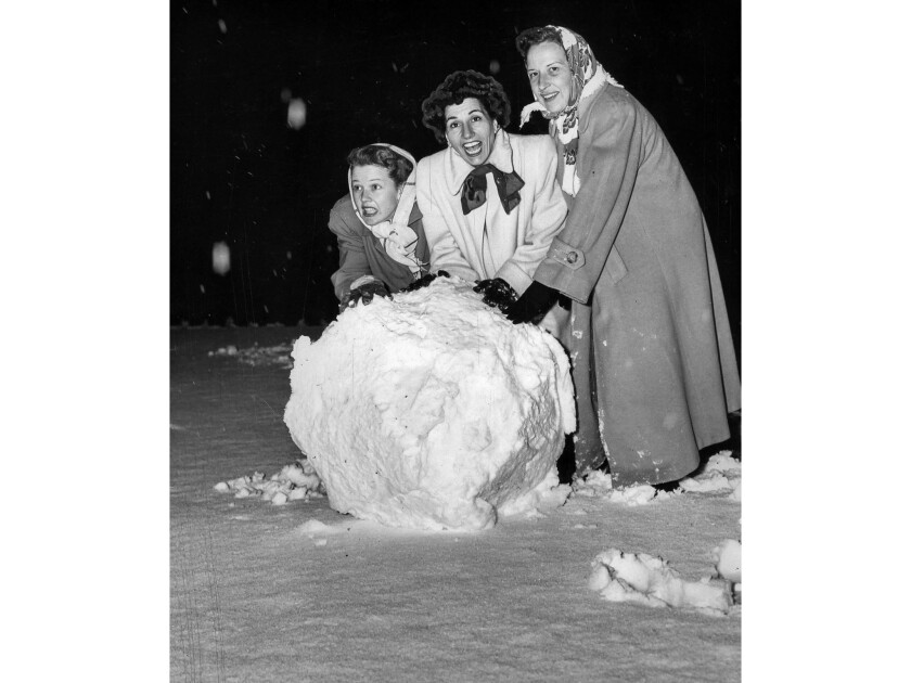 Jan. 11, 1949: Jean Rogers, Mrs. Ted Fio Rito and Mrs. Harvey Holp roll a big snowball in a front ya