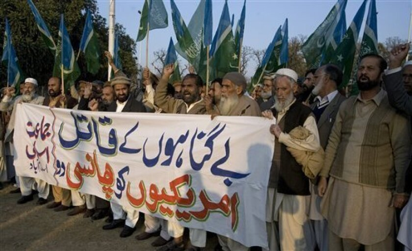 """Supporters of Pakistani religious party Jamat-e-Islami chant slogans behind a banner reading, """"hang the American killer of innocents"""", during a demonstration against a U.S. consular employee who is the lead suspect in the shooting deaths of two Pakistani men, in Islamabad, Pakistan, Sunday, Jan. 30"""