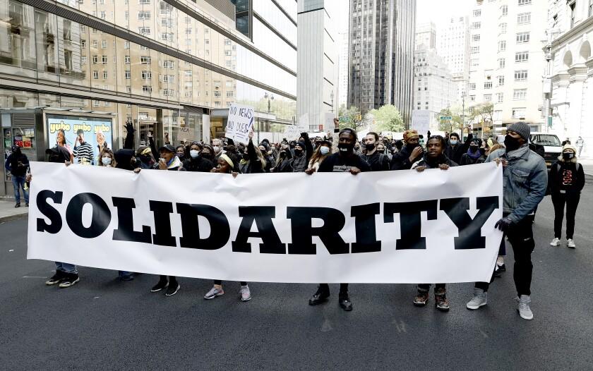 Les manifestants défilent dans la rue avec une bannière de solidarité devant eux.