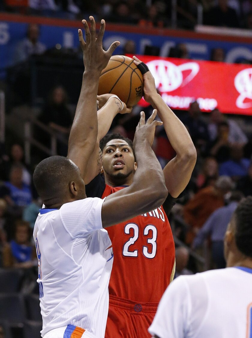 New Orleans Pelicans forward Anthony Davis (23) shoots as Oklahoma City Thunder forward Serge Ibaka, left, defends, in the first quarter of an NBA basketball game in Oklahoma City, Thursday, Feb. 11, 2016. (AP Photo/Sue Ogrocki)