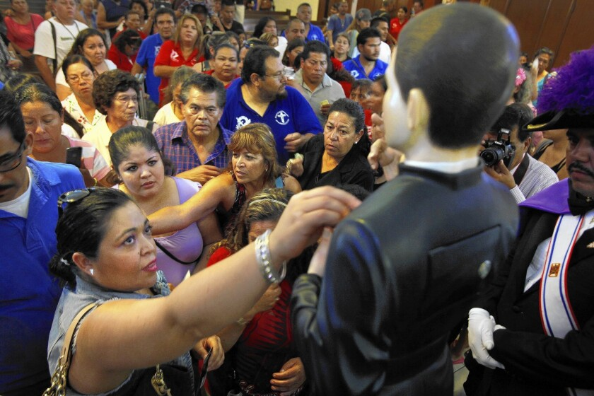 Parishioners gather at St. Marcellinus Catholic Church in the City of Commerce to honor Santo Toribio Romo Gonzalez. They took turns touching the most sacred part of the 4-foot-tall statue, his chest, which contains a bone from the saint's left ankle.