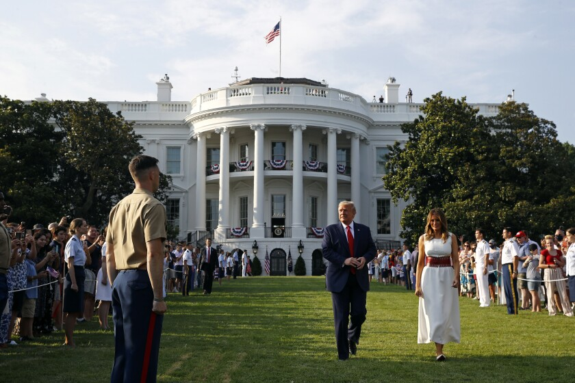 "President Donald Trump and first lady Melania Trump walk on the South Lawn of the White House during a ""Salute to America"""