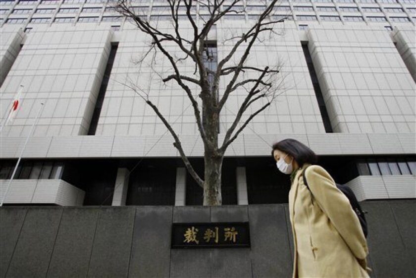 A woman walks by Tokyo District Court during a trial of 19-year-old Richard Hinds of Memphis, Tenn., in Tokyo, Monday, March 4, 2013. Japanese prosecutors say the American man accused of killing Irish exchange student Nicola Furlong in Tokyo has shown no remorse and should be punished severely. Hin