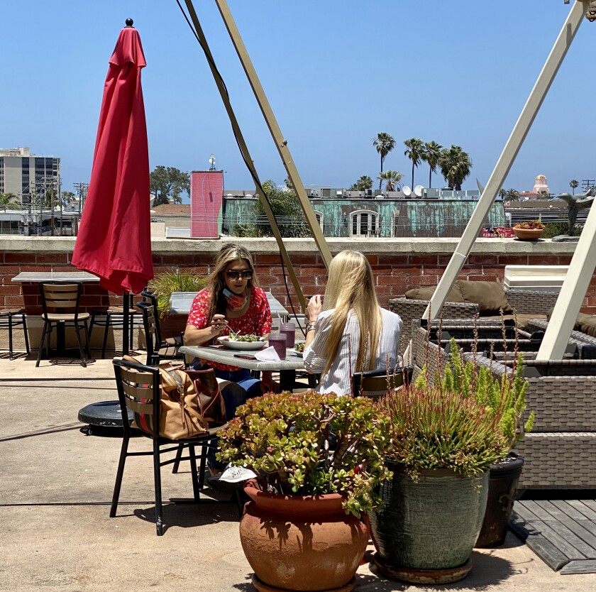 Customers eat at Trilogy Sanctuary's newly reopened rooftop cafe May 22 in La Jolla. Tables are spaced 10 feet apart for social distancing.