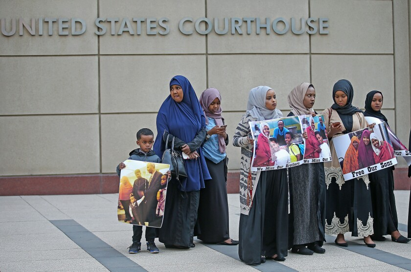 Supporters and family members of three men on trial rally outside the U.S.