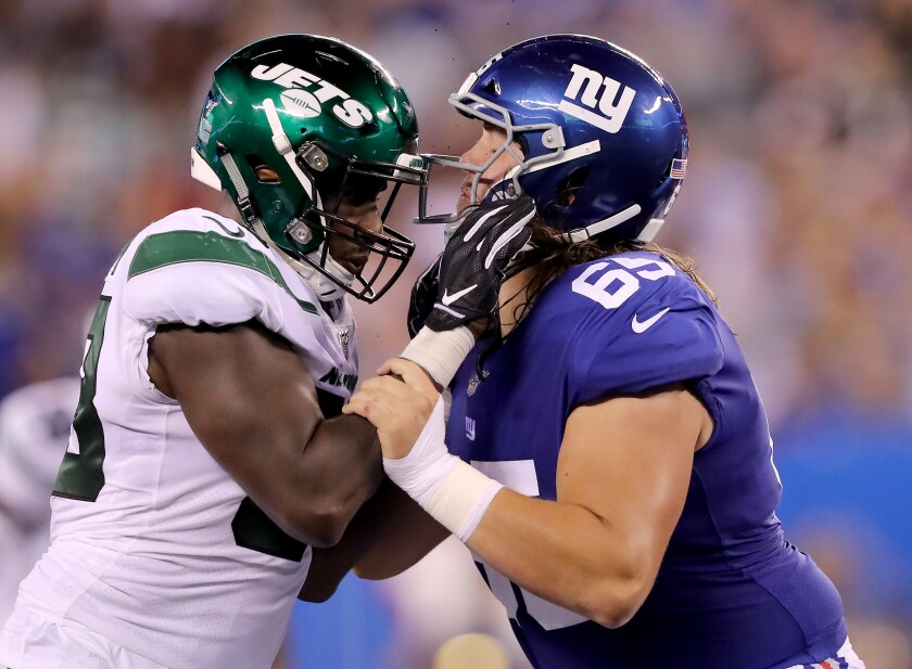 New York Jets linebacker Tarell Basham New York Giants guard Nick Gates battle for position during a preseason game Aug. 8 at MetLife Stadium.