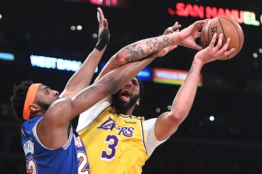 Lakers Anthony Davis is fouled by New York Knicks Mitchell Robinson in the first quarter at the Staples Center on Jan. 7.