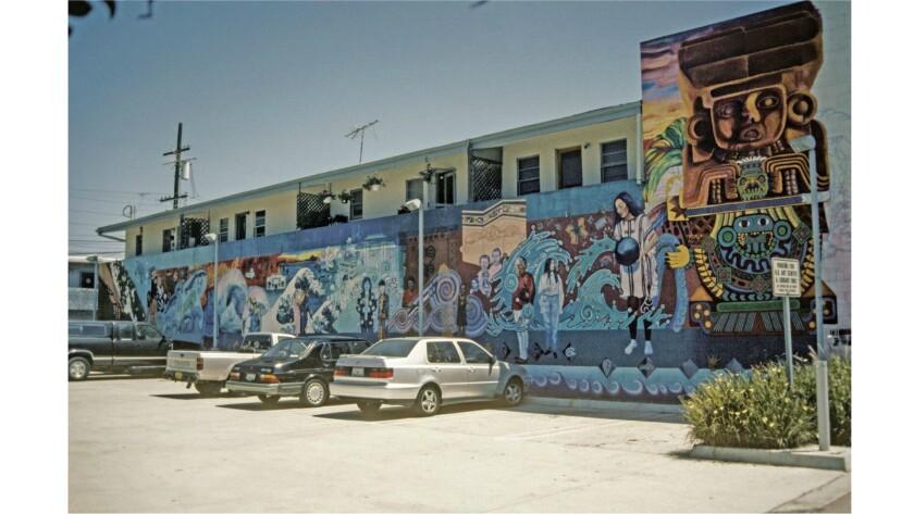 """The mural """"La Historia de Adentro/La Historia de Afuera"""" in Huntington Beach in progress in 1995."""