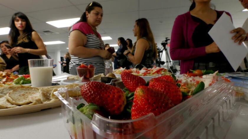 """Visitantes de L.A. Kitchen observan las opciones saludables del menú luego de la puesta en marcha de la campaña """"Healty Eating Out"""" (Comer saludable fuera de casa), del Departamento de Salud Pública del Condado de Los Ángeles (Luis Sinco / Los Angeles Times)."""