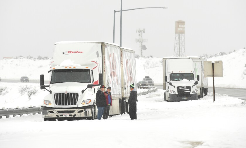 Truckers stand along Interstate 15 in the Cajon Pass on Thursday waiting to be towed.
