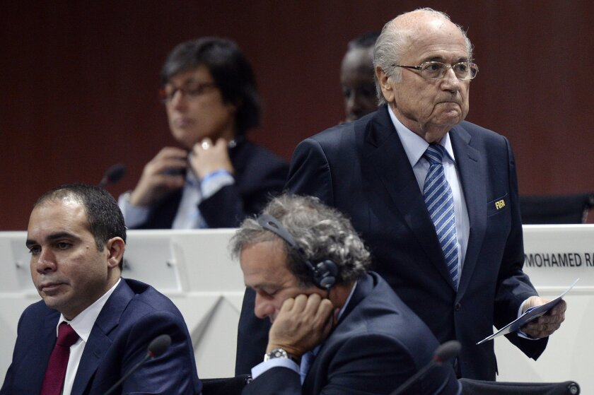 FILE - In this May 29, 2015 file photo FIFA president Joseph S. Blatter, right, walks past Prince Ali bin al-Hussein, left, and UEFA President Michel Platini, center, during the 65th FIFA Congress held at the Hallenstadion in Zurich, Switzerland. In a FIFA election that is now more open than expect