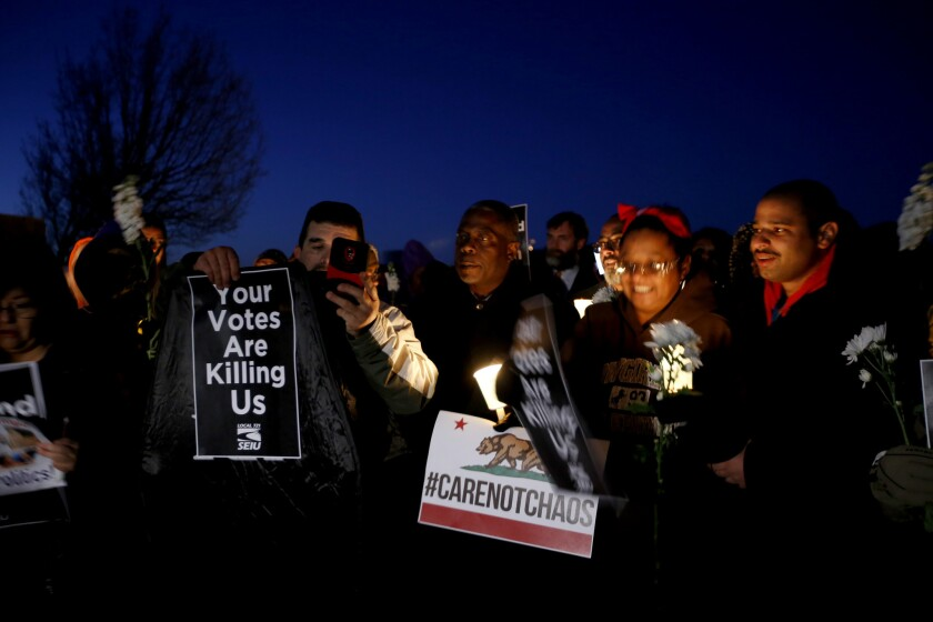 Demonstrators hold a candlelight vigil in Lancaster in 2017 to demand a town hall meeting with Rep. Steve Knight (R-Palmdale) to discuss the Trump administration's immigration and healthcare policies.