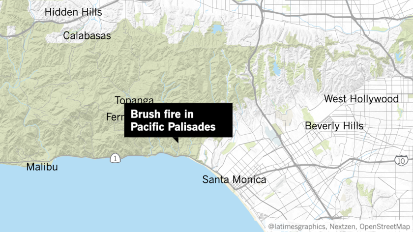 Firefighters were battling a fast-moving brush fire that had grown to 30 acres and was threatening homes in Pacific Palisades.