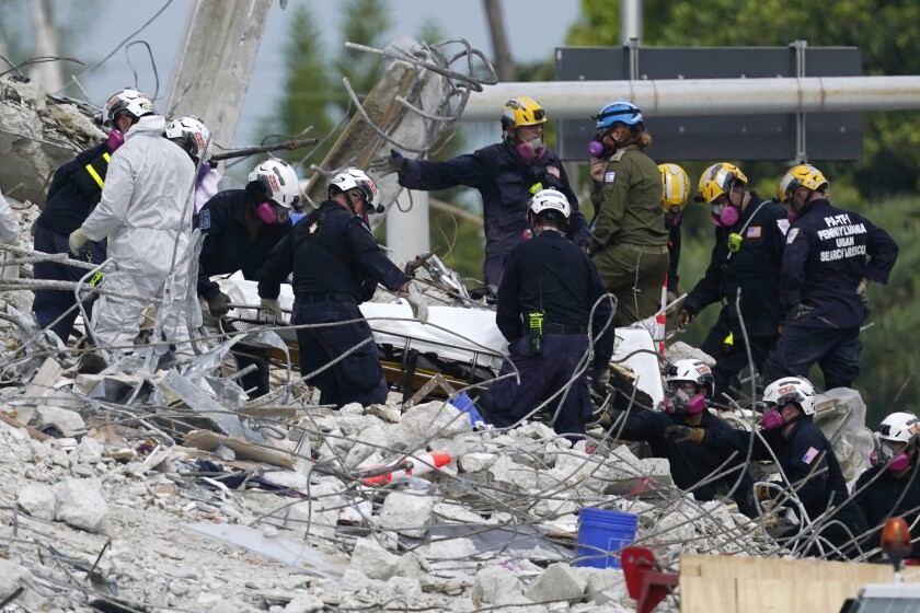 Rescue workers move a stretcher containing recovered remains at the site of the collapsed Champlain Towers South condo building, Monday, July 5, 2021 in Surfside, Fla. The remaining structure was demolished Sunday, which partially collapsed June 24. Many people remain unaccounted for. (AP Photo/Lynne Sladky)