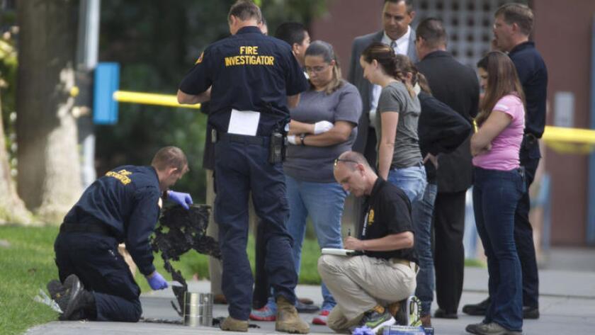 Investigadores de incendios y homicidios de San Diego reúnen evidencia de la escena de un ataque a una persona sin hogar en el centro de San Diego, temprano el miércoles. Este es el cuarto ataque a desamparados en menos de una semana.
