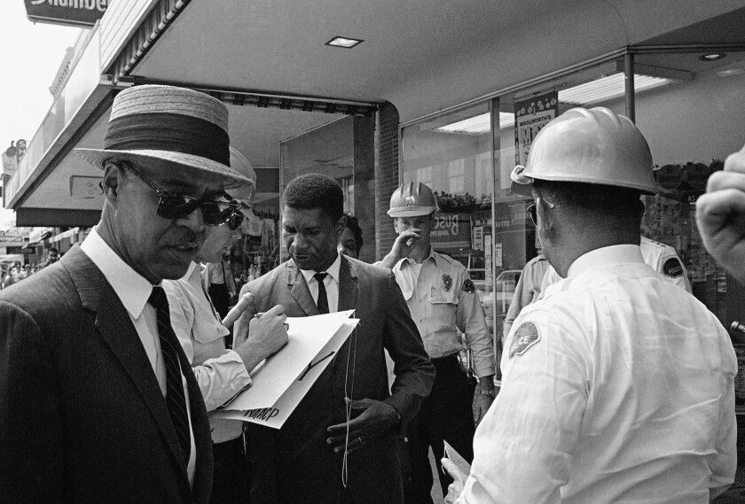Roy Wilkins, left, executive secretary of the NAACP, and Medgar Evers, center, field secretary of the NAACP, are arrested for picketing in downtown Jackson, Miss.