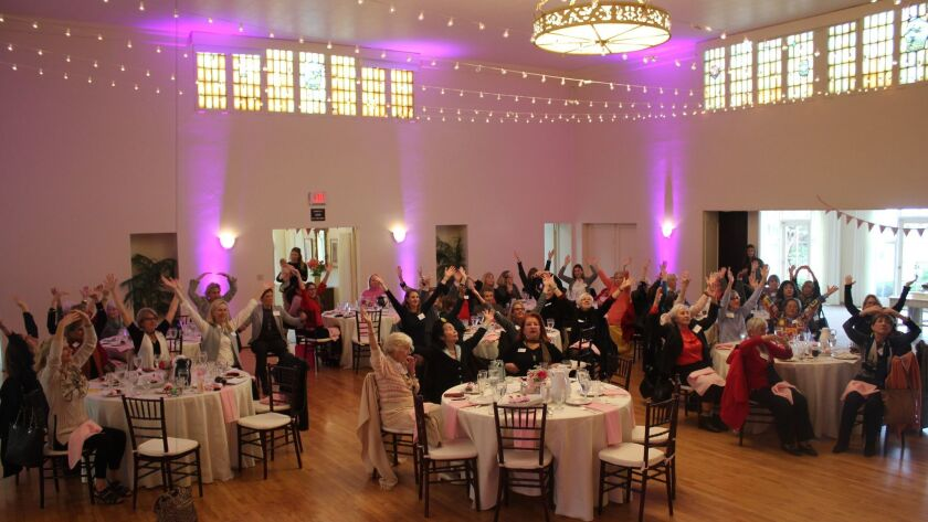 La Jolla Woman's Club members and luncheon attendees practice healthy stretches.