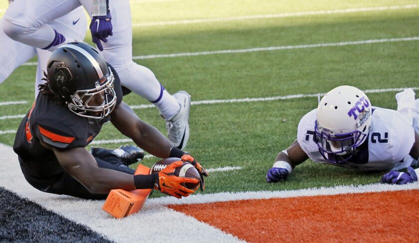 Oklahoma State running back Jeff Carr, left, stretches to get the ball over the goal line for a touchdown in front of TCU cornerback Torrance Mosley (2) in the second quarter of an NCAA college football game in Stillwater, Okla., Saturday, Nov. 7, 2015. (AP Photo/Sue Ogrocki)