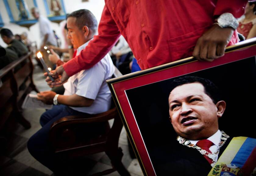 A Venezuelan Embassy staffer holds a picture of President Hugo Chavez at a service devoted to the sick in Regla, Cuba. The Venezuelan leader is recovering from surgery in Cuba.